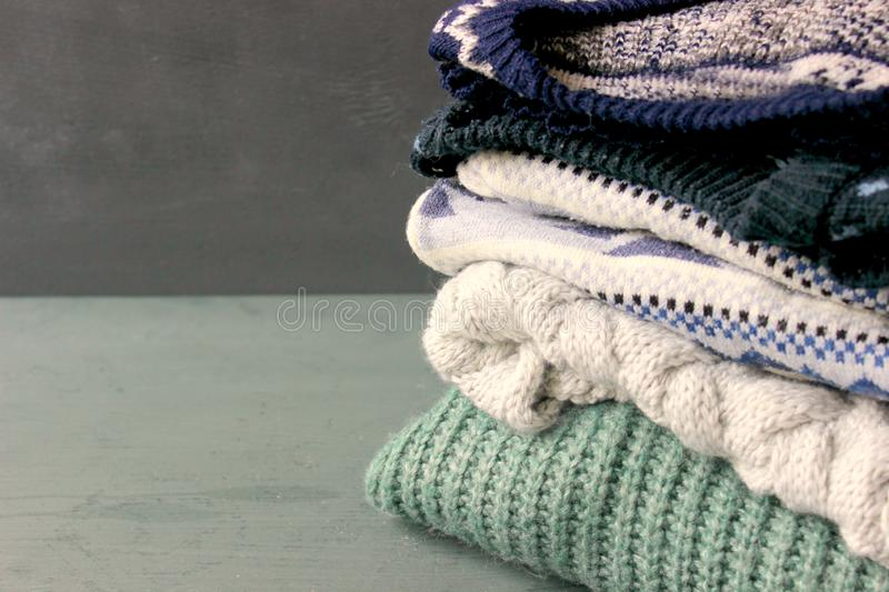 A stack of cozy knitted sweaters, a copy of space royalty free stock image