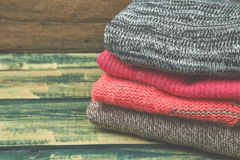 Stack of cozy knitted sweaters. A pile of warm sweaters on a wooden table on green rustic background. Autumn and winter clothes. royalty free stock photography