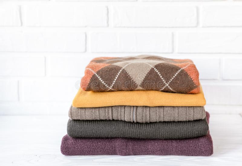 Stack of cozy knitted sweaters preparing warm clothes for autumn season concept. Stack of cozy knitted sweaters on the white background preparing warm clothes royalty free stock photos