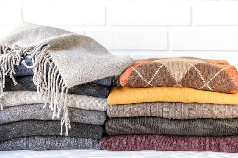 Stack of cozy knitted sweaters preparing warm clothes for autumn winter seasons concept. stock images