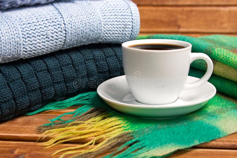 Stack of cozy knitted warm sweater and a scarf . Sweaters in retro Style and a Cup of coffee. The concept of warmth and comfort stock photo