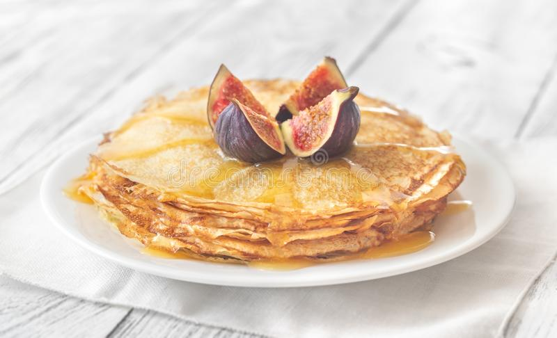 Stack of crepes on the white plate. Stack of homemade crepes with fresh fig and sweet topping on the white plate royalty free stock photo