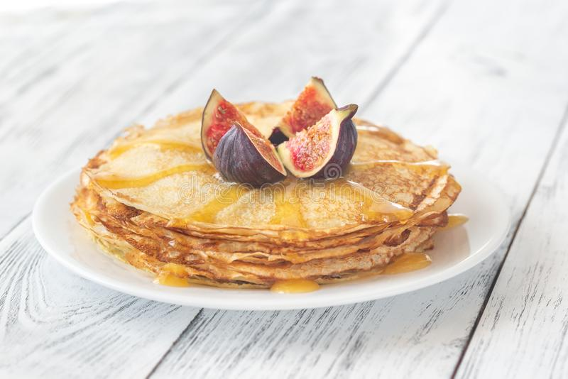 Stack of crepes on the white plate. Stack of homemade crepes with fresh fig and sweet topping on the white plate royalty free stock images