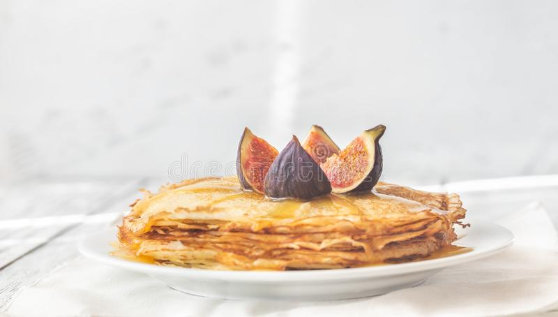 Stack of crepes on the white plate. Stack of homemade crepes with fresh fig and sweet topping on the white plate stock photos