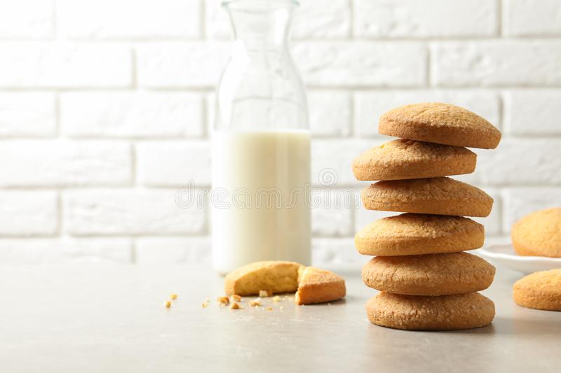 Stack of Danish butter cookies and milk on table against brick wall. Space for text royalty free stock photo