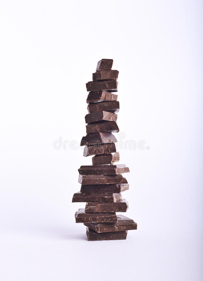 Stack of delicious dark chocolate pieces on a white background. royalty free stock image