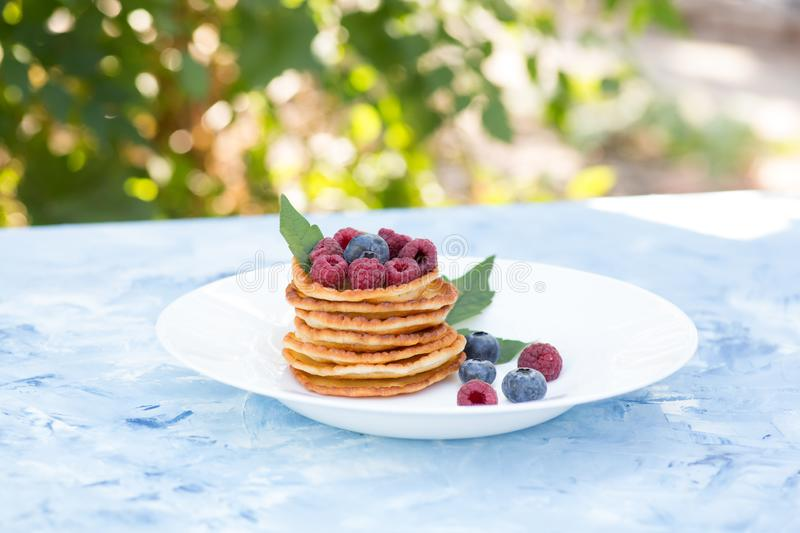 A stack of delicious pancakes with sour cream, raspberries and blueberries on a light background. with copy space royalty free stock images