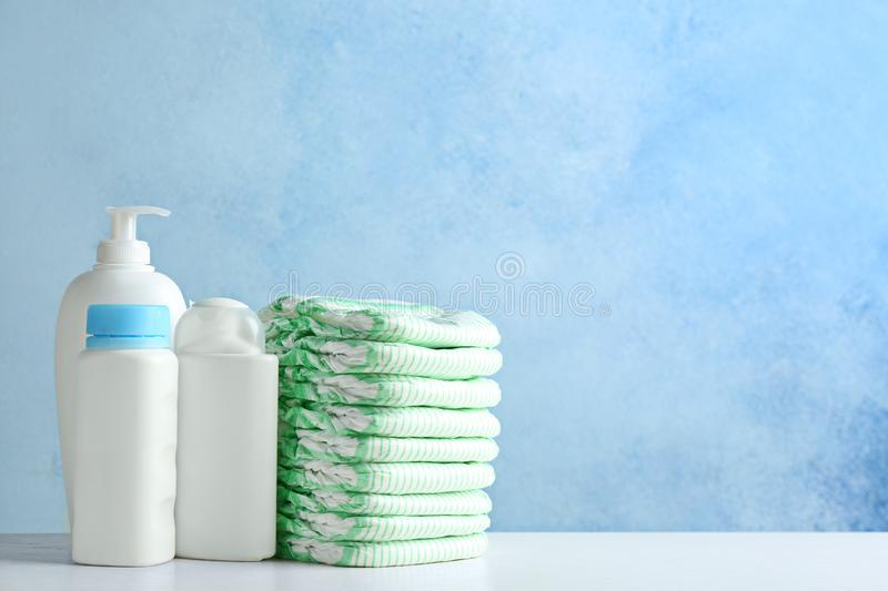 Stack of diapers and toiletries on table against color background. Baby accessories royalty free stock image