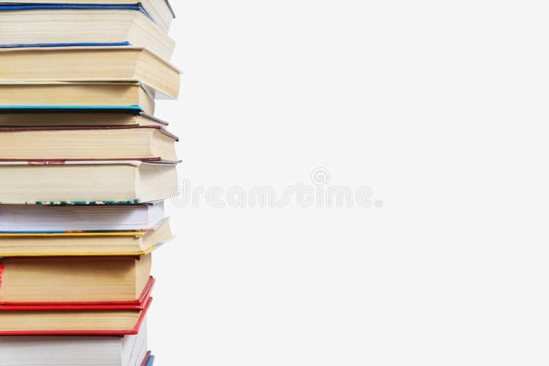 Stack of different books on a table against a white wall background royalty free stock photo
