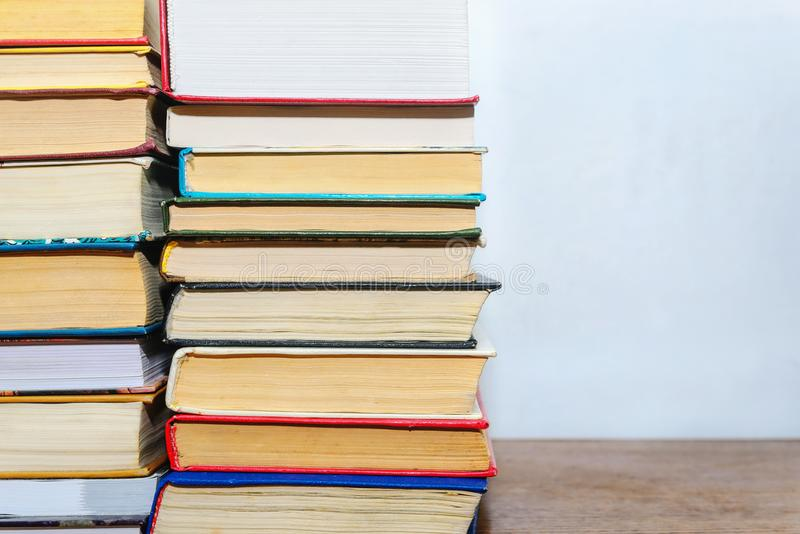 Stack of different books on a table against a white wall background stock photo