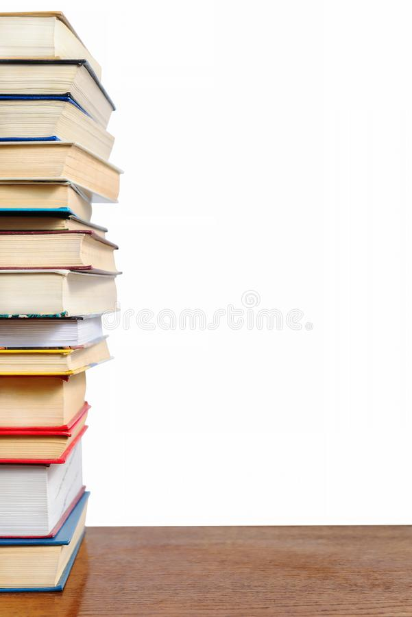 A stack of different books on a table against stock photos
