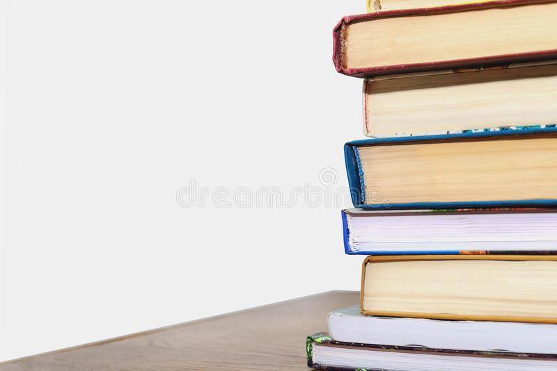 Stack of different books on a table against a white wall background stock photos