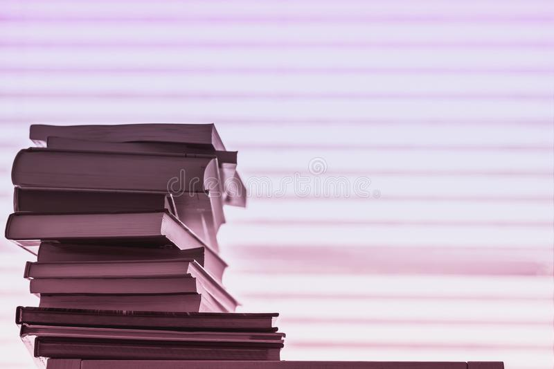 Stack of different books, textbooks against a light striped pink violet background with copy space. Concept of of stock photo