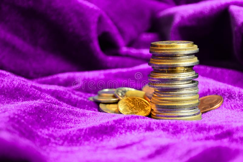 Stack of different European coins on purple velvet background. Close up. stock photo