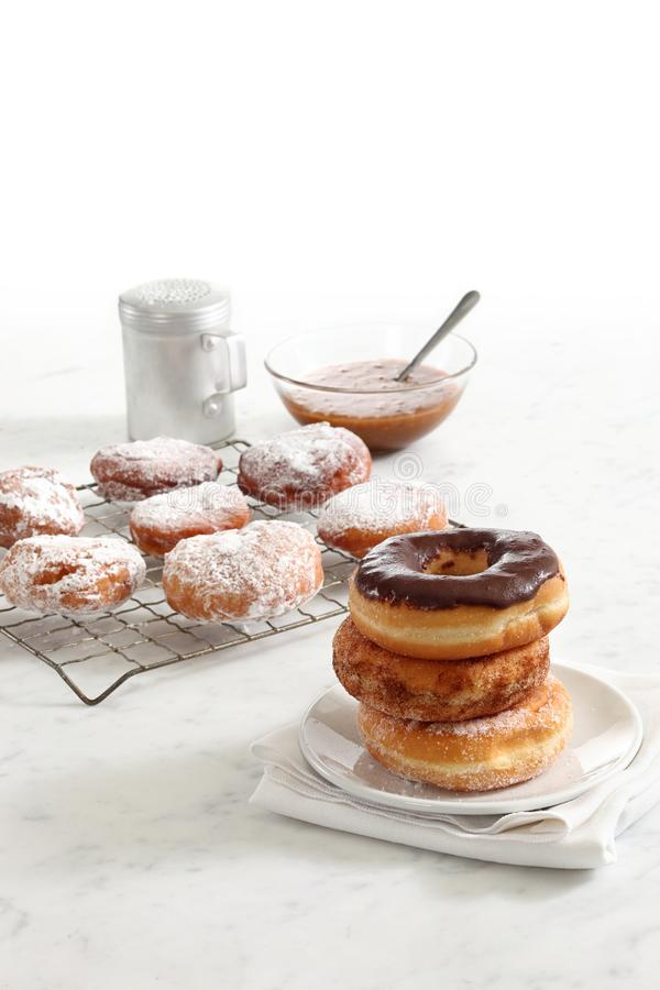Dougnuts stacked on plate. Stack of donuts on a plate with freshly baked doughnuts in the background royalty free stock photos