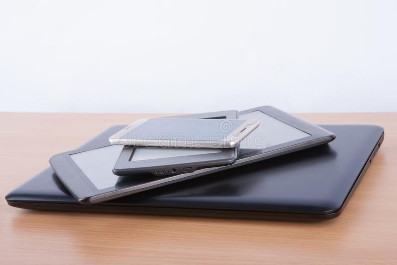 Stack of electronic gadgets on a table - notebook, tablet, ebook reader and a smatphone stock photography