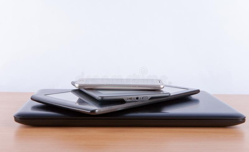 Stack of electronic gadgets on a table - notebook, tablet, ebook reader and a smatphone on the top stock photo