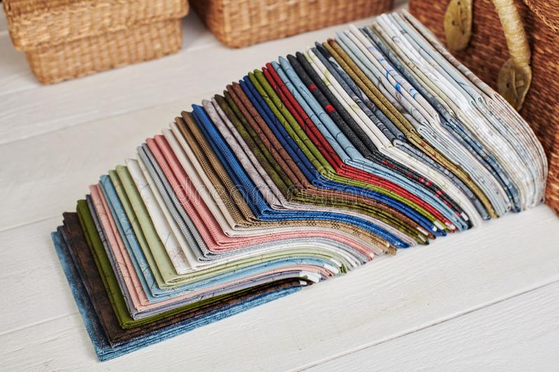 Stack of fat quarters of colorful quilting fabrics on the background of baskets royalty free stock photo