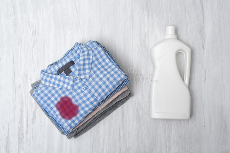 Stack foldable dirty linen and a bottle of liquid for washing. Top view royalty free stock image