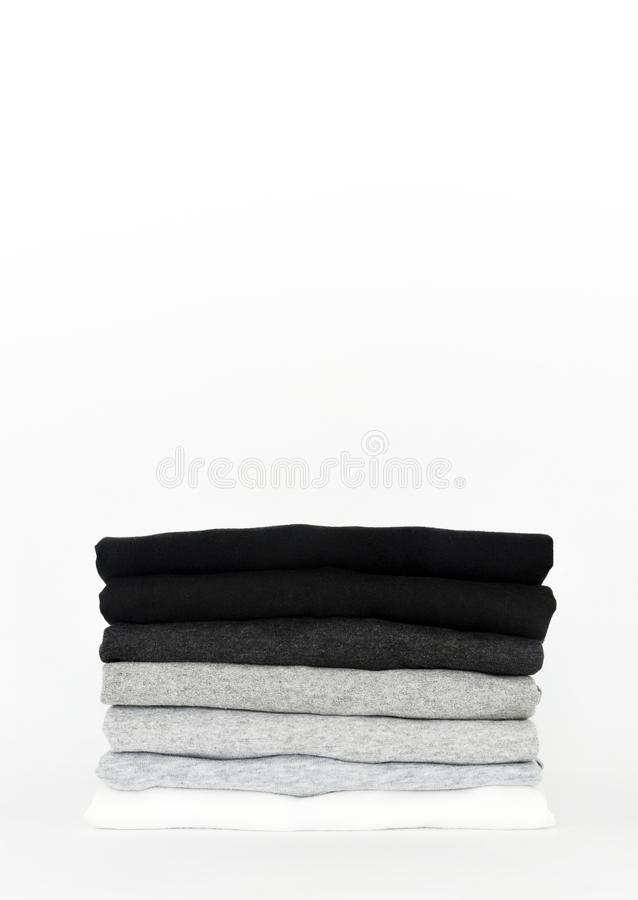Stack of folded black, grey and white color monochrome t-shirt on white background stock image