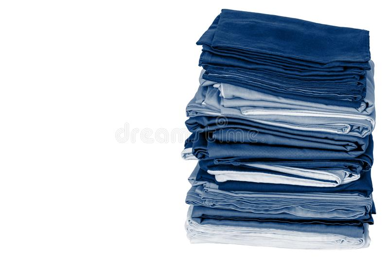 Stack of folded clean blue bedding on a white background: duvet covers, sheets, pillowcases. Close-up. Copy space stock image