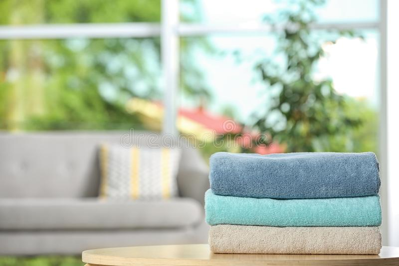 Stack of folded clean soft towels on table indoors. Space for text stock images