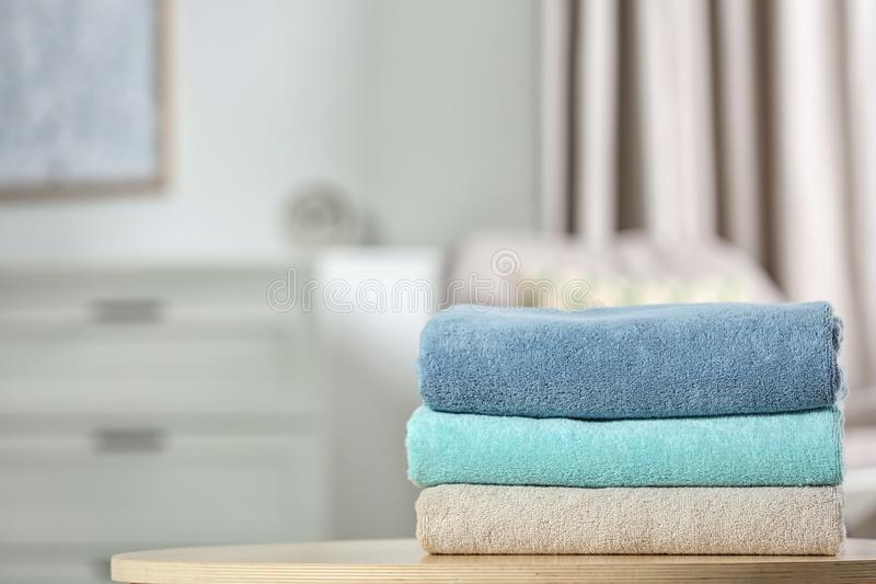 Stack of folded clean soft towels on table indoors. Space for text royalty free stock photo