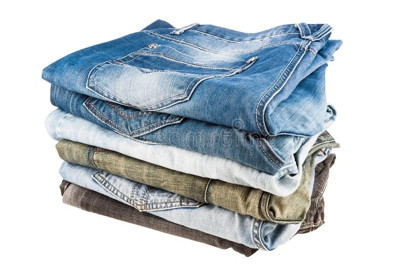 Stack of folded clothes, blue jeans pants, dark blue denim trousers. Isolated on white background royalty free stock photography