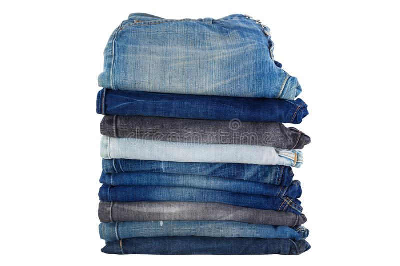 Stack of folded clothes, blue jeans pants, dark blue denim trousers isolated on white. royalty free stock photos