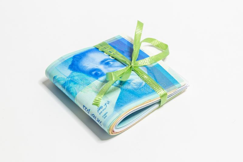 A stack of folded new Israeli banknotes of different value in shekels NIS tied with green ribbon isolated on a white backgroun. D royalty free stock photos