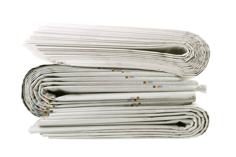 Stack of folded newspapers. A stack of tabloid format folded newspapers isolated on white background royalty free stock photos