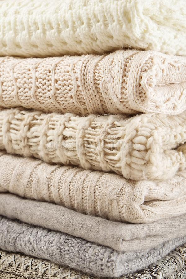 Stack of warm winter clothes close up. Sweaters background texture stock photos