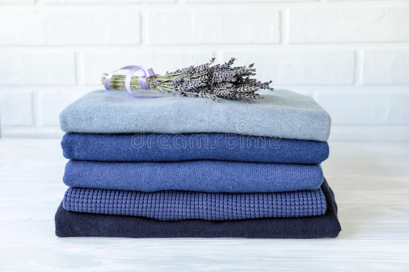 Stack of folded warm knitted men`s sweaters in blue and a bunch of dried lavender, care of clothes aroma and protection stock image