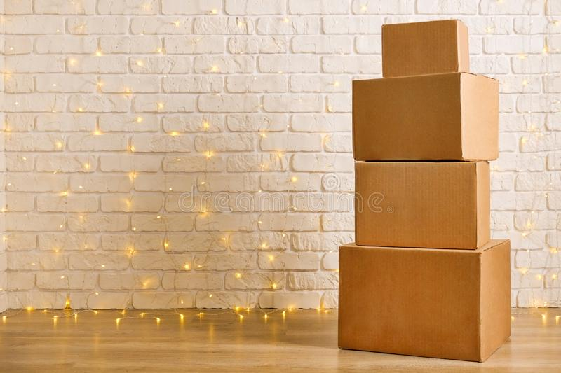 Corrugated fiberboard boxes with christmas lights on background stock image
