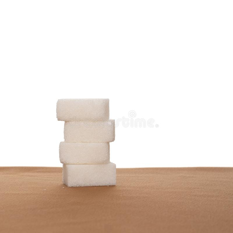 Stack of four sugar cubes on fabric, white background. Healthy eating. royalty free stock images
