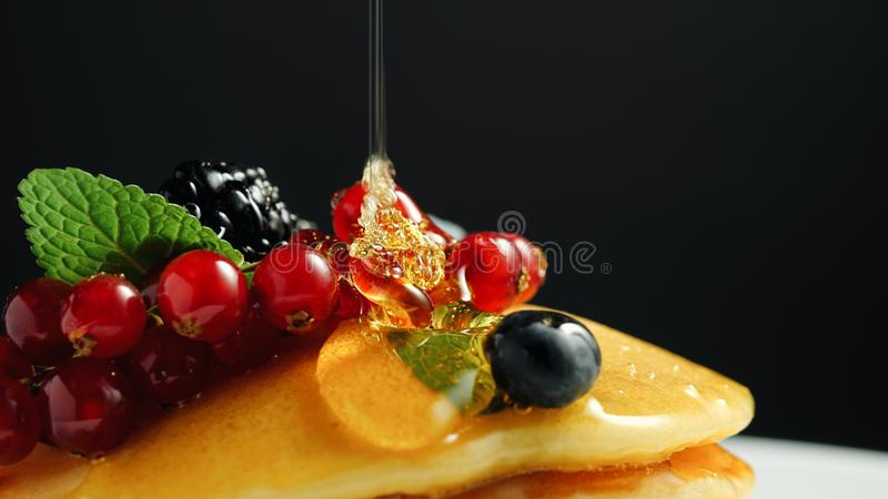 Stack of fresh fluffy pancakes decorated on top with forest berries on plate and pouring honey syrup. Delicious, healthy royalty free stock image
