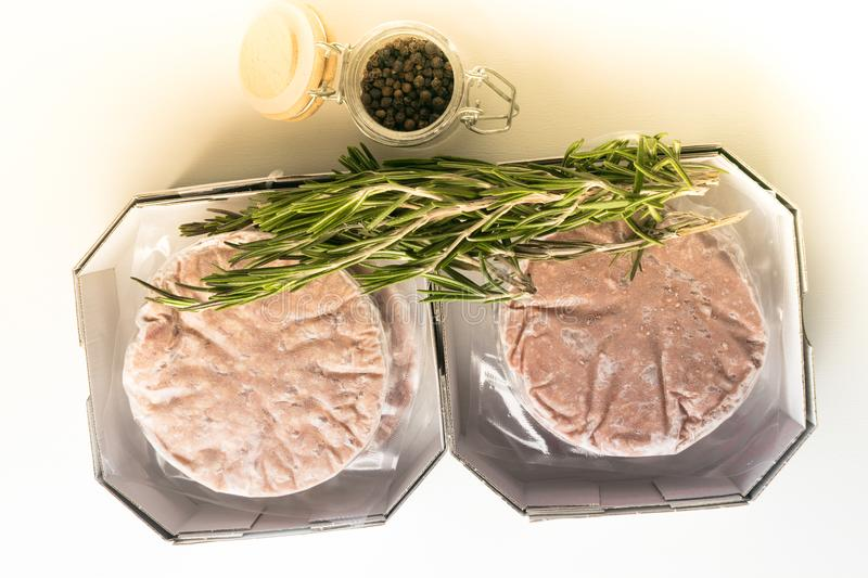 Stack of fresh raw burger patty with black pepper isolated on white. Bio raw Minced burger Meat with pepper Prepared for Grilling in paper box stock images