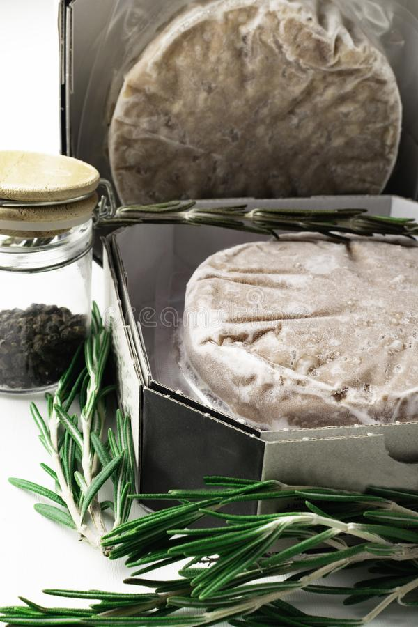 Stack of fresh raw burger patty with black pepper isolated on white. Stack of fresh raw burger patty isolated on white with rosemary and jar with black pepper royalty free stock photography