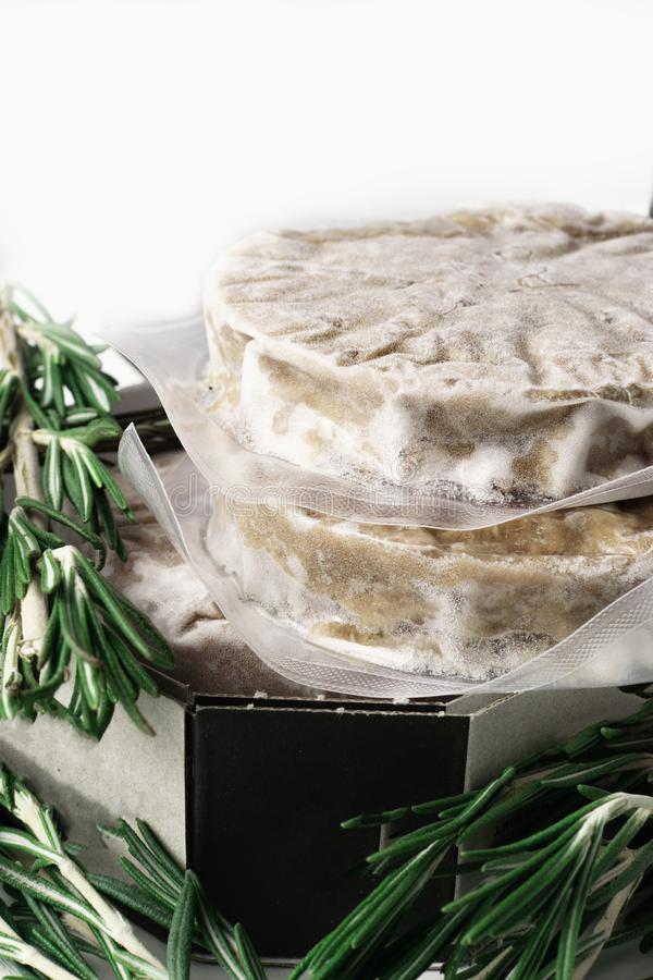 Stack of fresh raw burger patty isolated on white. With rosemary stock image