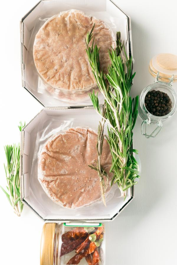 Stack of fresh raw burger patty with black pepper isolated on white. Stack of fresh raw burger patty isolated on white with rosemary and jar with black pepper stock photo