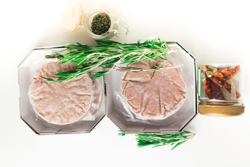 Stack of fresh raw burger patty with black pepper isolated on white. Stack of fresh raw burger patty isolated on white with rosemary and jar with black pepper stock images