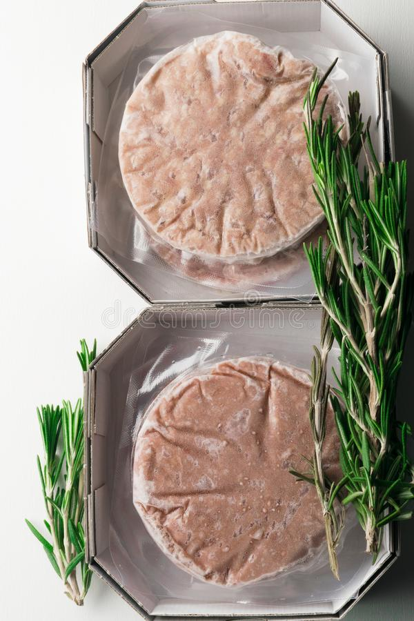 Stack of fresh raw burger patty isolated on white. With rosemary stock photo