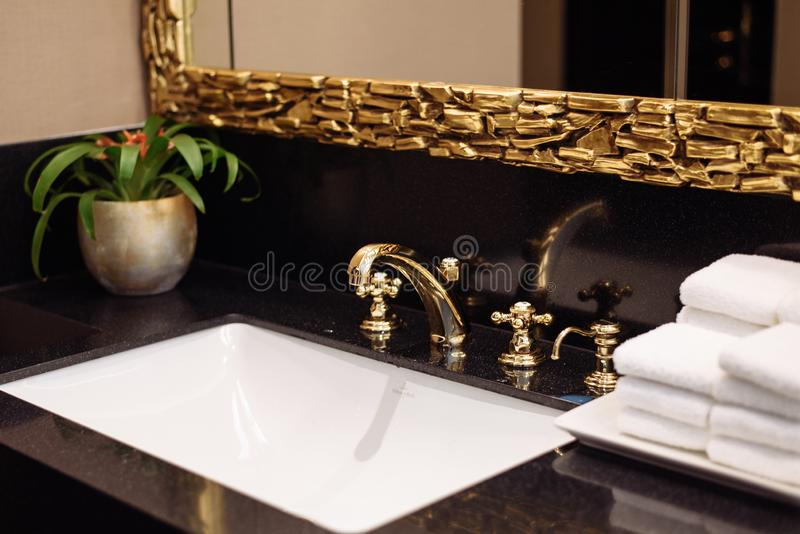 A stack of fresh white towels in the hotel`s luxurious bathroom. A gold faucet, mirror and marble sink in a public restroom of an royalty free stock photography