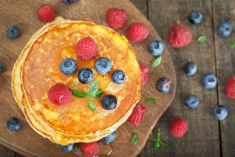 Stack of freshly baked american pancakes on wooden board royalty free stock photo