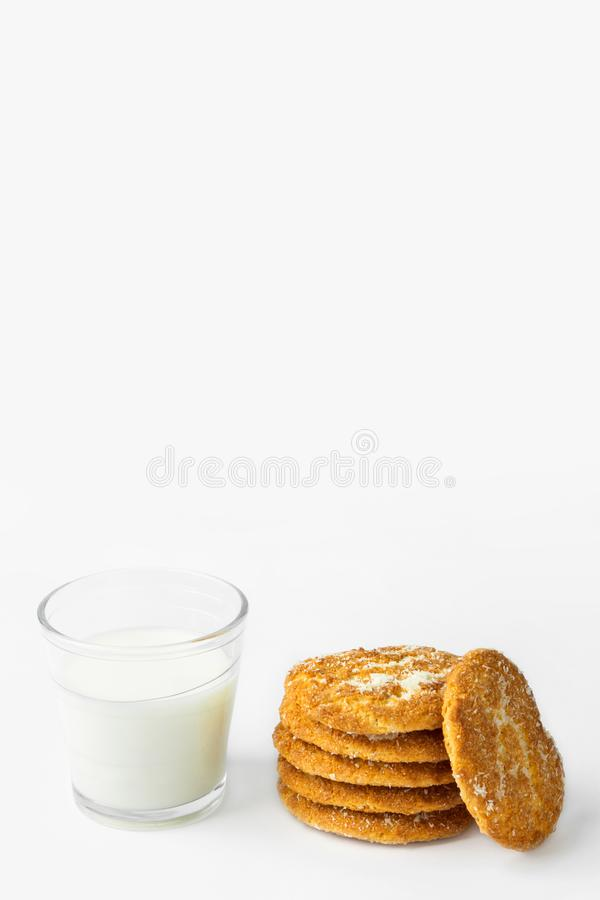 Stack of freshly home baked oatmeal and coconut biscuits glass of milk on white kitchen table wall background. Australian anzac stock image