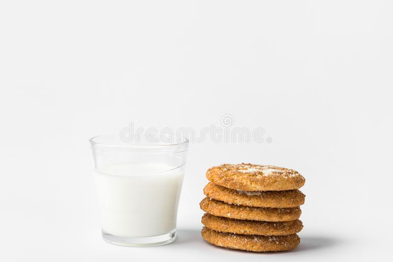 Stack of freshly home baked oatmeal and coconut cookies and glass of milk on white kitchen table. Australian anzac biscuits stock photo