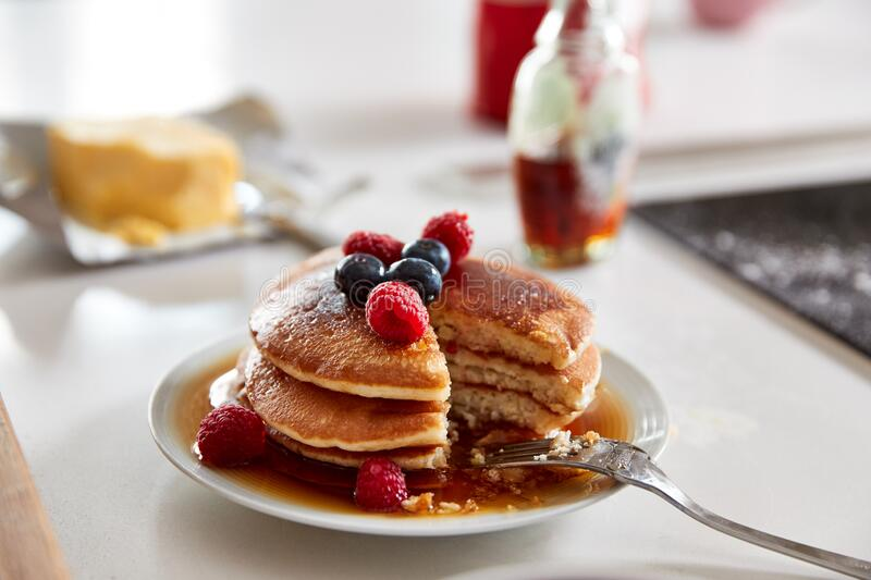 Stack Of Freshly Made Pancakes Or Crepes With Maple Syrup And Berries On Table For Pancake Day stock photos