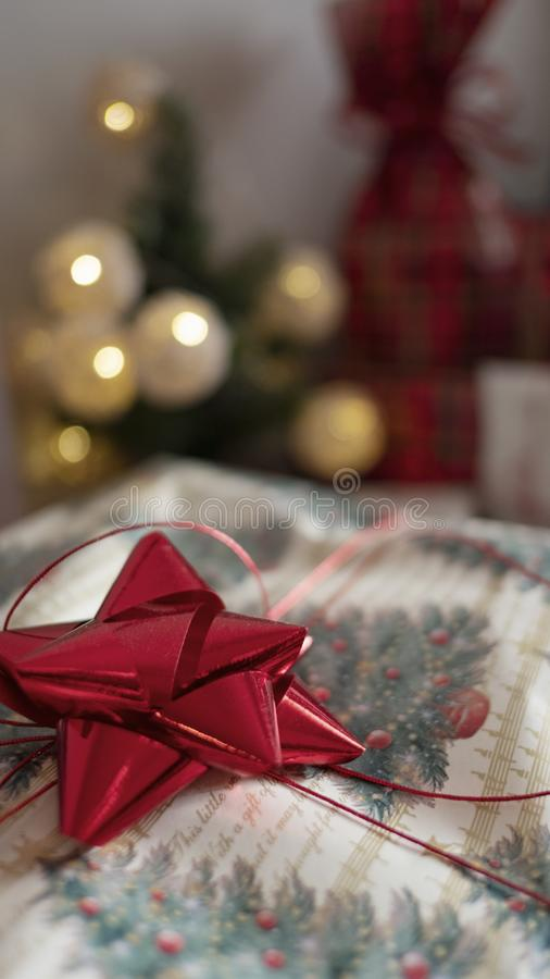 Stack of gifts wrapped in festive Christmas paper with season specific print, red shiny bows and red metallic tinsel string rope. Vertical shot with selective royalty free stock photos