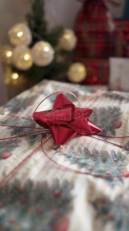 Stack of gifts wrapped in festive Christmas paper with season specific print, red shiny bows and red metallic tinsel string rope. Vertical shot with selective stock photos