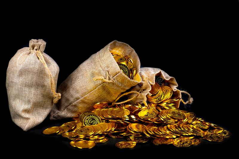 Stack gold coin in treasure sack. Lots of gold coin in treasure sack at black background stock images